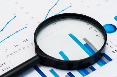 magnifying glass on graphs and spreadsheet
